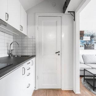Idéer för nordiska linjära svart kök, med en nedsänkt diskho, släta luckor, vita skåp, vitt stänkskydd, stänkskydd i tunnelbanekakel, mellanmörkt trägolv och brunt golv