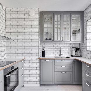 Idéer för att renovera ett avskilt, litet skandinaviskt vit vitt u-kök, med luckor med glaspanel, grå skåp, laminatbänkskiva, vitt stänkskydd, stänkskydd i tunnelbanekakel, ljust trägolv, en nedsänkt diskho, rostfria vitvaror och beiget golv