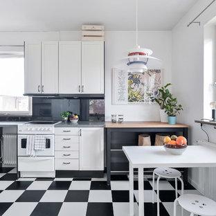 Foto på ett minimalistiskt grå kök, med skåp i shakerstil, vita skåp, svart stänkskydd, glaspanel som stänkskydd, vita vitvaror och flerfärgat golv