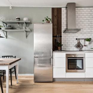Foto på ett mellanstort minimalistiskt kök, med släta luckor, vita skåp, vitt stänkskydd, stänkskydd i tunnelbanekakel, rostfria vitvaror, ljust trägolv och beiget golv