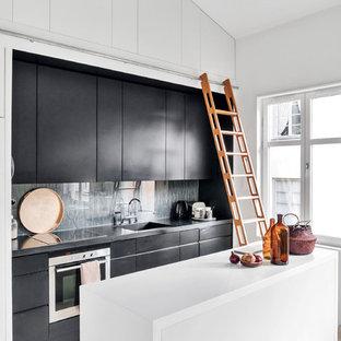 Bild på ett funkis grå grått parallellkök, med släta luckor, svarta skåp, grått stänkskydd, rostfria vitvaror, en köksö och grått golv