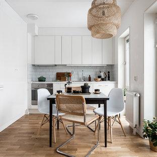 Idées déco pour une cuisine américaine linéaire scandinave de taille moyenne avec un placard à porte plane, des portes de placard blanches, une crédence blanche, une crédence en carrelage métro, un électroménager en acier inoxydable, un sol en bois clair et aucun îlot.