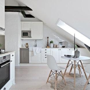 Inspiration för ett mellanstort, avskilt nordiskt grå grått l-kök, med vita skåp, vitt stänkskydd, stänkskydd i mosaik, rostfria vitvaror, beiget golv, en rustik diskho, luckor med upphöjd panel och ljust trägolv