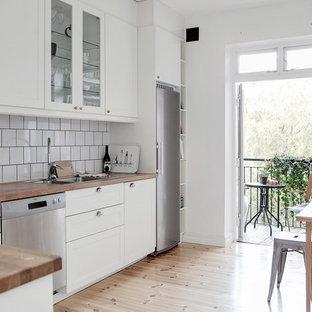 Exempel på ett skandinaviskt kök, med en dubbel diskho, skåp i shakerstil, vita skåp, träbänkskiva, vitt stänkskydd, rostfria vitvaror, ljust trägolv och beiget golv