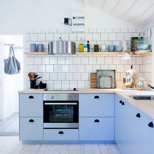 Mid-sized scandinavian kitchen pictures - Inspiration for a mid-sized scandinavian l-shaped painted wood floor kitchen remodel in Stockholm with a single-bowl sink, flat-panel cabinets, blue cabinets, wood countertops, stainless steel appliances, no island and white backsplash