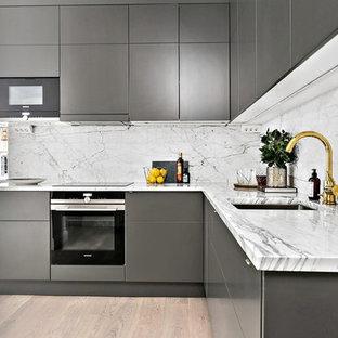 Idéer för att renovera ett mycket stort funkis l-kök, med en undermonterad diskho, släta luckor, grå skåp, vitt stänkskydd, stänkskydd i sten, svarta vitvaror och ljust trägolv