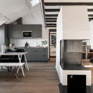 Inspiration för ett nordiskt linjärt kök med öppen planlösning, med släta luckor, grå skåp, vitt stänkskydd, integrerade vitvaror och brunt golv
