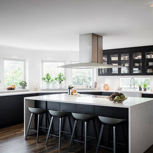 Inspiration för stora minimalistiska vitt kök, med luckor med glaspanel, svarta skåp, en rustik diskho, mörkt trägolv, en köksö och brunt golv