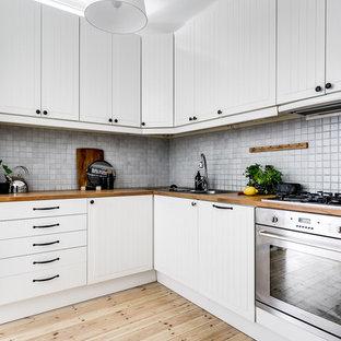 Inspiration för små skandinaviska beige kök, med vita skåp, träbänkskiva, grått stänkskydd, ljust trägolv, en nedsänkt diskho, rostfria vitvaror, beiget golv och luckor med profilerade fronter