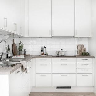 Idéer för att renovera ett nordiskt beige beige l-kök, med en dubbel diskho, släta luckor, vita skåp, träbänkskiva, vitt stänkskydd, rostfria vitvaror, ljust trägolv och beiget golv