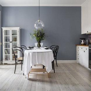 Exempel på ett minimalistiskt kök, med släta luckor, vita skåp och ljust trägolv