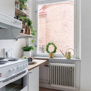 Nordisk inredning av ett avskilt, mellanstort linjärt kök, med släta luckor, vita skåp, träbänkskiva, vita vitvaror och linoleumgolv