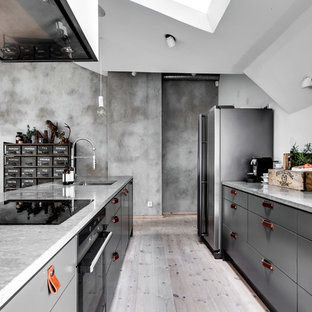 Industrial open concept kitchen appliance - Example of an urban single-wall light wood floor and gray floor open concept kitchen design in Stockholm with flat-panel cabinets, gray cabinets, concrete countertops and an island