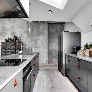 Foto på ett industriellt linjärt kök med öppen planlösning, med släta luckor, grå skåp, bänkskiva i betong, ljust trägolv, en köksö och grått golv