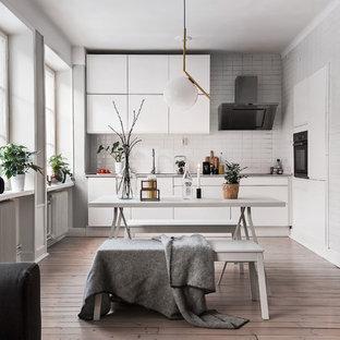 Cette photo montre une petite cuisine ouverte scandinave avec un placard à porte plane, des portes de placard blanches, une crédence blanche, un sol en bois foncé et un électroménager noir.