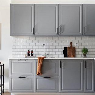 Idéer för små vintage vitt l-kök, med grå skåp, laminatbänkskiva, vitt stänkskydd, stänkskydd i porslinskakel, integrerade vitvaror, ljust trägolv, beiget golv och luckor med upphöjd panel