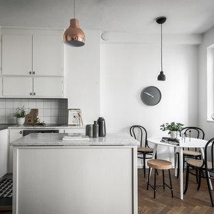 Imagen de cocina comedor en L, escandinava, pequeña, con fregadero integrado, armarios con paneles lisos, puertas de armario blancas, salpicadero blanco, electrodomésticos de acero inoxidable, suelo de madera oscura, una isla y encimera de mármol