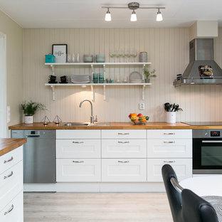 Idéer för mellanstora nordiska kök, med en nedsänkt diskho, skåp i shakerstil, vita skåp, träbänkskiva, beige stänkskydd, rostfria vitvaror och ljust trägolv