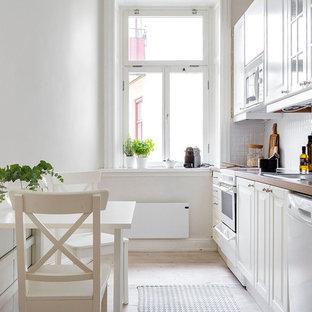 Idéer för att renovera ett mellanstort skandinaviskt linjärt kök och matrum, med en nedsänkt diskho, luckor med upphöjd panel, vita skåp, vitt stänkskydd, vita vitvaror, ljust trägolv, träbänkskiva och stänkskydd i keramik