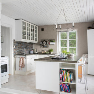 Bild på ett mellanstort lantligt kök, med luckor med glaspanel, vita skåp, ljust trägolv, en köksö, bänkskiva i betong, brunt stänkskydd och stänkskydd i stickkakel