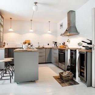 Inredning av ett nordiskt mellanstort kök, med luckor med profilerade fronter, grå skåp, träbänkskiva, stänkskydd i porslinskakel, vita vitvaror, målat trägolv, en köksö, vitt golv och vitt stänkskydd