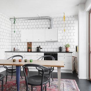 Bild på ett minimalistiskt svart svart kök, med en nedsänkt diskho, släta luckor, vita skåp, vitt stänkskydd, svarta vitvaror och svart golv