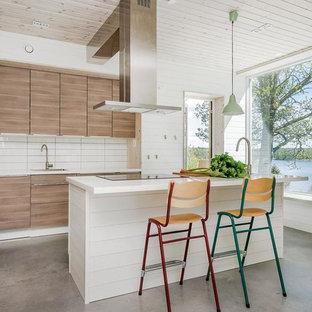 Modern inredning av ett stort linjärt kök, med släta luckor, skåp i mellenmörkt trä, vitt stänkskydd, integrerade vitvaror, betonggolv, en köksö och grått golv