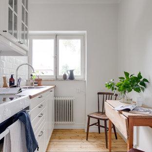 Nordisk inredning av ett avskilt beige linjärt beige kök, med en nedsänkt diskho, luckor med upphöjd panel, vita skåp, träbänkskiva, vitt stänkskydd, stänkskydd i tunnelbanekakel, vita vitvaror, ljust trägolv och beiget golv