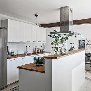 Idéer för mellanstora nordiska brunt kök, med träbänkskiva, ljust trägolv, en köksö, vitt golv, en dubbel diskho, släta luckor, vita skåp, vitt stänkskydd, stänkskydd i tunnelbanekakel och rostfria vitvaror