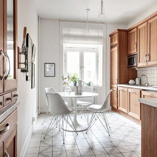 Mittelgroße Skandinavische Wohnküche ohne Insel in L-Form mit Schrankfronten mit vertiefter Füllung, hellbraunen Holzschränken, Granit-Arbeitsplatte, Küchenrückwand in Weiß, Zementfliesen und buntem Boden in Göteborg