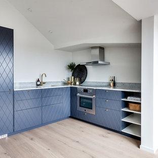 Bild på ett mellanstort minimalistiskt l-kök, med en enkel diskho, blå skåp, rostfria vitvaror, ljust trägolv och marmorbänkskiva