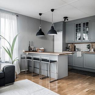 Foto på ett skandinaviskt brun kök, med luckor med upphöjd panel, grå skåp, träbänkskiva, vitt stänkskydd, stänkskydd i keramik, vita vitvaror, mellanmörkt trägolv, en halv köksö och beiget golv
