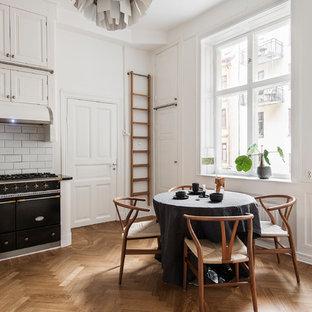 Idéer för att renovera ett skandinaviskt svart svart kök, med luckor med upphöjd panel, beige skåp, vitt stänkskydd, stänkskydd i tunnelbanekakel, svarta vitvaror och mellanmörkt trägolv