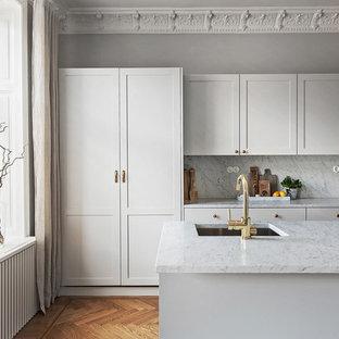Exempel på ett stort nordiskt parallellkök, med en enkel diskho, luckor med infälld panel, vita skåp, marmorbänkskiva och mellanmörkt trägolv