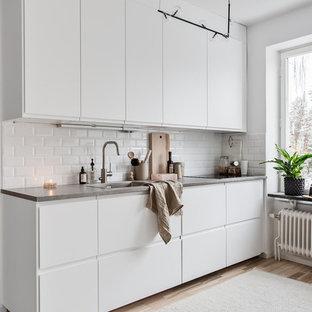 Inspiration för ett nordiskt kök, med släta luckor, vita skåp, bänkskiva i betong, en enkel diskho, vitt stänkskydd, stänkskydd i tunnelbanekakel, ljust trägolv och beiget golv