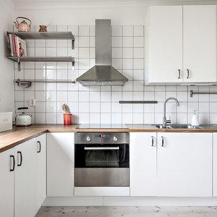Inredning av ett skandinaviskt l-kök, med en nedsänkt diskho, släta luckor, vita skåp, träbänkskiva, vitt stänkskydd, rostfria vitvaror, ljust trägolv och grått golv