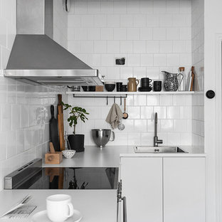 Design ideas for a small scandinavian l-shaped separate kitchen in Gothenburg with a single-bowl sink, flat-panel cabinets, white cabinets, laminate benchtops, white splashback, porcelain splashback, stainless steel appliances, ceramic floors and no island.
