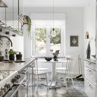 Inspiration för nordiska grått kök, med släta luckor, vita skåp, rostfria vitvaror och grått golv