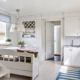 Foto på ett mellanstort maritimt kök, med släta luckor, vita skåp, vitt stänkskydd, stänkskydd i tunnelbanekakel, ljust trägolv och beiget golv