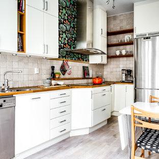 Inredning av ett nordiskt linjärt kök och matrum, med en nedsänkt diskho, släta luckor, vita skåp, träbänkskiva, beige stänkskydd, stänkskydd i stenkakel, rostfria vitvaror, ljust trägolv och beiget golv