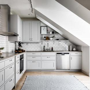 Foto på ett mellanstort minimalistiskt brun kök, med grå skåp, träbänkskiva, vitt stänkskydd, stänkskydd i tunnelbanekakel, rostfria vitvaror och ljust trägolv