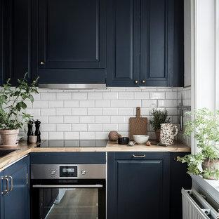Modelo de cocina en L, escandinava, pequeña, cerrada, sin isla, con fregadero de un seno, armarios con paneles con relieve, puertas de armario azules, encimera de madera, salpicadero blanco, salpicadero de azulejos tipo metro, electrodomésticos de acero inoxidable y encimeras beige