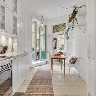 Inredning av ett skandinaviskt mellanstort linjärt kök och matrum, med en enkel diskho, luckor med infälld panel, vita skåp, rostfria vitvaror, ljust trägolv och beiget golv