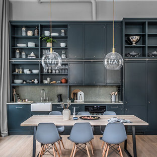 Photo of a mid-sized contemporary single-wall eat-in kitchen in Stockholm with a farmhouse sink, flat-panel cabinets, green cabinets, concrete benchtops, grey splashback, medium hardwood floors, no island and beige floor.
