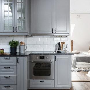 Idéer för mellanstora minimalistiska linjära svart kök, med en undermonterad diskho, luckor med upphöjd panel, grå skåp, vitt stänkskydd, stänkskydd i tunnelbanekakel, mellanmörkt trägolv och brunt golv
