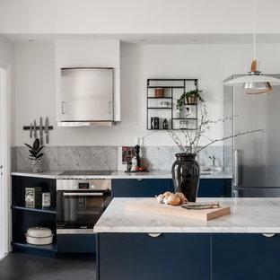 Idéer för att renovera ett minimalistiskt grå grått parallellkök, med en undermonterad diskho, släta luckor, blå skåp, marmorbänkskiva, grått stänkskydd, stänkskydd i marmor, rostfria vitvaror, en halv köksö och svart golv