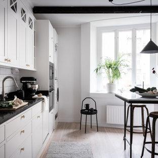 Bild på ett minimalistiskt svart linjärt svart kök, med en undermonterad diskho, släta luckor, vita skåp, vitt stänkskydd, stänkskydd i tunnelbanekakel, rostfria vitvaror och en halv köksö