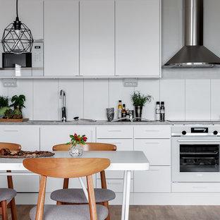 Inspiration för ett skandinaviskt grå linjärt grått kök och matrum, med släta luckor, vita skåp, vita vitvaror, mellanmörkt trägolv och brunt golv