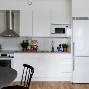 Inspiration för ett funkis grå linjärt grått kök med öppen planlösning, med en undermonterad diskho, släta luckor, vita skåp, vita vitvaror, mellanmörkt trägolv och brunt golv