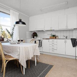 Idéer för ett minimalistiskt kök och matrum, med släta luckor, vita skåp, bänkskiva i rostfritt stål, vitt stänkskydd, vita vitvaror och beiget golv